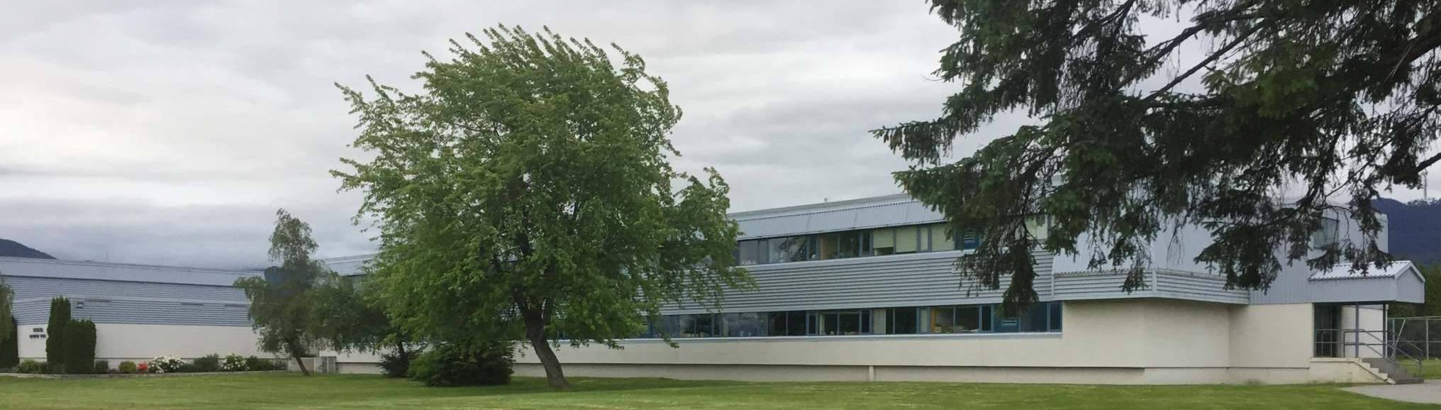 side view of a school building with trees in forefront